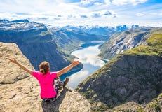 La gente feliz se relaja en acantilado durante el viaje Noruega Trolltunga que camina la ruta imagen de archivo libre de regalías