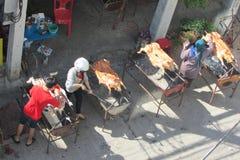 La gente frigge le carcasse dei maiali sullo sputo Fotografia Stock