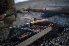 La gente frigge le salsiccie su un fuoco aperto fotografia stock