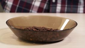 La gente getta i chicchi di caffè arrostiti di caduta in un piatto sul primo piano 4K della tavola archivi video
