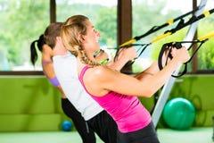 La gente in ginnastica di sport sull'addestratore della sospensione fotografie stock