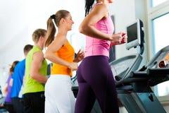 La gente in ginnastica su funzionamento della pedana mobile immagine stock libera da diritti