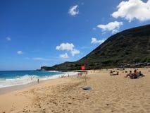 La gente gioca alla spiaggia con il segno della forte corrente sulla spiaggia Fotografie Stock