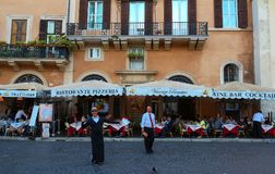 La gente gode del loro pranzo ad uno dei molti ristoranti nel quadrato di Navona, Roma Fotografia Stock