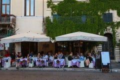 La gente gode del loro pranzo ad uno dei molti ristoranti nel quadrato di Navona, Roma Immagine Stock