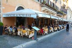 La gente gode del loro pranzo ad uno dei molti ristoranti nel quadrato di Navona, Roma Fotografie Stock