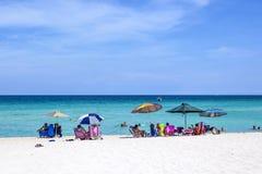 La gente gode della sabbia e del resto sotto un ombrello al beautifu Fotografie Stock Libere da Diritti