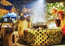 La gente goza de la comida tradicional en el mercado de la Navidad de Riga en la noche Fotos de archivo