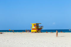 La gente goza de la playa al lado de una torre del salvavidas Imagen de archivo libre de regalías
