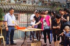 La gente goza del cerdo de carne asada en la adoración del templo Imagenes de archivo