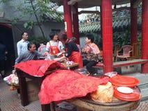 La gente goza del cerdo de carne asada en la adoración del templo Foto de archivo