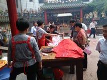 La gente goza del cerdo de carne asada en la adoración del templo Fotografía de archivo