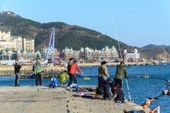 La gente goza el pescar en la bahía de Xinghai Pasatiempo chino Fotografía de archivo libre de regalías
