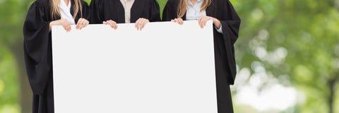 La gente graduada que sostenía una tarjeta en blanco contra verde empañó el fondo fotos de archivo libres de regalías