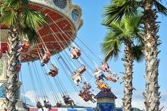 La gente guida sul carosello al parco di divertimenti Fotografia Stock Libera da Diritti
