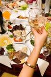 La gente ha cena su un banchetto. Immagini Stock