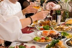 La gente ha cena su un banchetto. Fotografie Stock