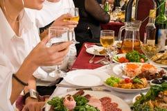 La gente ha cena su un banchetto. Fotografia Stock Libera da Diritti