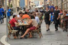 La gente habla en una tabla en un café al aire libre Foto de archivo libre de regalías