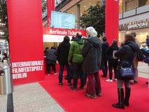 La gente hace cola para arriba delante de una cabina que vende los boletos para el festival de cine de Berlinale Imagen de archivo libre de regalías