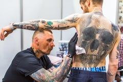La gente hace tatuajes en el 10mo convenio internacional del tatuaje en el centro de la Congreso-EXPO Foto de archivo