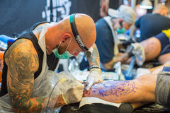 La gente hace tatuajes en el 10mo convenio internacional del tatuaje en el centro de la Congreso-EXPO Imágenes de archivo libres de regalías