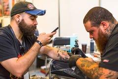 La gente hace tatuajes en el 10mo convenio internacional del tatuaje en el centro de la Congreso-EXPO Fotos de archivo libres de regalías