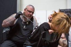 La gente hace tatuajes en el 10mo convenio internacional del tatuaje en el centro de la Congreso-EXPO Fotos de archivo