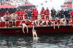 La gente immerge per recuperare un incrocio di legno gettato nel mare, du Fotografia Stock Libera da Diritti