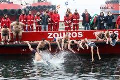 La gente immerge per recuperare un incrocio di legno gettato nel mare, du Immagine Stock Libera da Diritti
