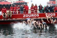 La gente immerge per recuperare un incrocio di legno gettato nel mare, du Immagine Stock