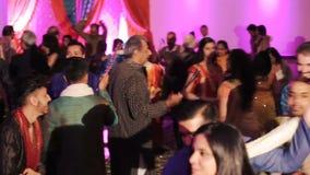 La gente india lucha con los palillos mientras que ella baila almacen de video