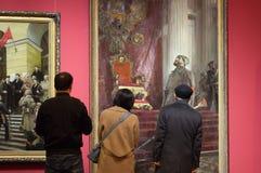 La gente instruida mayor delante de una pintura nombrada el ` el día es perdido ` Foto de archivo