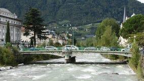 La gente italiana conduce el coche y el paseo en el río del transeúnte de la cruce del puente en Meran almacen de metraje de vídeo
