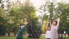 La gente joven activa está ejercitando en el parque que hace los ejercicios de la yoga que se colocan en las esteras en día calie almacen de video