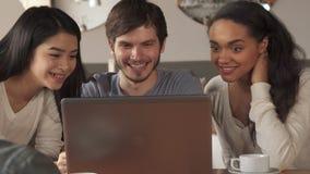 La gente joven agita sus manos a la pantalla del ordenador portátil en el café almacen de metraje de vídeo