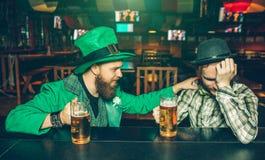 La gente joven bebida se sienta en el contador de la barra en pub Individuo en traje verde tocar a su amigo El hombre joven en iz imagen de archivo