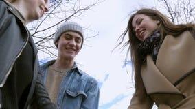 La gente joven camina en el parque, dice las noticias, comunica, ríe Buen humor Ponga sus manos juntas almacen de metraje de vídeo