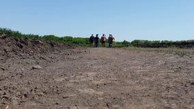 La gente joven camina a lo largo de una carretera nacional entre campos de trigo almacen de video