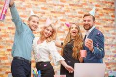 La gente joven celebra algo en un partido corporativo en la oficina fotos de archivo libres de regalías