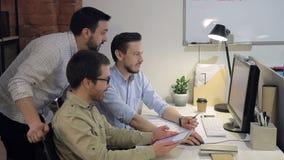 La gente joven de los hombres de negocios en oficina mira en la pantalla del ordenador y de la tableta que comparan y que analiza almacen de video