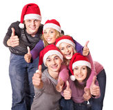 La gente joven del grupo en el sombrero de santa muestra los pulgares para arriba. Imágenes de archivo libres de regalías