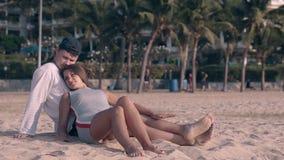 La gente joven descansa sobre la arena de la orilla de la tarde en la luz de la puesta del sol almacen de video