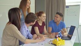 La gente joven discute algo en el ordenador portátil en la oficina almacen de metraje de vídeo