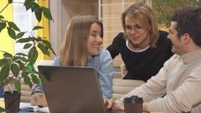 La gente joven discute un cierto proyecto sobre el ordenador portátil metrajes