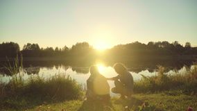 La gente joven disfruta de resto por el río durante puesta del sol Muchachas con amanecer de la reunión del individuo almacen de video
