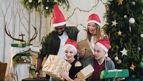 La gente joven divertida está compartiendo los regalos con decoraciones de la Navidad y un árbol de navidad hermoso Celebración d almacen de metraje de vídeo