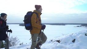 La gente joven el invierno camina en las montañas, backpackers que caminan en nieve almacen de video