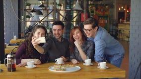 La gente joven emocional está tomando el selfie con el smartphone que presenta y que ríe dentro del café moderno Tecnología moder almacen de metraje de vídeo