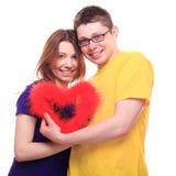 La gente joven en el amor que lleva a cabo el corazón y se acurruca Imagenes de archivo
